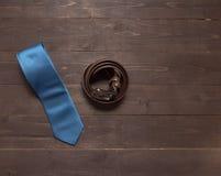 Κομψό σύνολο: μπλε δεσμός, καφετιά ζώνη δέρματος, στο ξύλινο backgro Στοκ Εικόνες