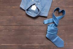 Κομψό σύνολο: μπλε πουκάμισο και μπλε γραβάτα, στο ξύλινο backgrou Στοκ Εικόνες