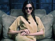 Κομψό φόρεμα μουστάρδας μόδας πρότυπο φορώντας, που κάθεται στον καναπέ Στοκ φωτογραφίες με δικαίωμα ελεύθερης χρήσης