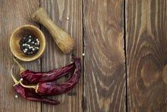 Κονίαμα και γουδοχέρι με το πιπέρι και καρυκεύματα στον ξύλινο πίνακα Στοκ φωτογραφία με δικαίωμα ελεύθερης χρήσης