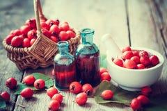 Κονίαμα των μούρων κραταίγου, tincture των μπουκαλιών και του μήλου αγκαθιών στο καλάθι Στοκ Εικόνες