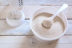 Κονιοποιημένος τύπος νηπίων σε ένα κουτάλι προετοιμάζοντας την πολτοποίηση τροφίμων παιδιών δίπλα σε ένα μπουκάλι μωρών στοκ φωτογραφία