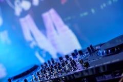Κονσόλα του DJ στο σκοτάδι ενάντια σε μια θολωμένη οθόνη στοκ φωτογραφία με δικαίωμα ελεύθερης χρήσης