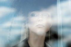 κοντά στη γυναίκα παραθύρ&omega Στοκ εικόνες με δικαίωμα ελεύθερης χρήσης