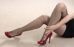 Κοντή φούστα, καλσόν διχτυών ψαρέματος και κόκκινα υψηλά τακούνια στοκ φωτογραφία