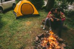 Κοντινού πυρκαγιά στρατόπεδων συνεδρίασης ζεύγους ιστορίες και τσαγιού και αφήγησης κατανάλωσης σκηνή και suv στο υπόβαθρο στοκ φωτογραφία