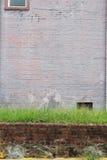 Κοντός τουβλότοιχος που ολοκληρώνεται με τη χλόη μπροστά από τον πορφυρό χρωματισμένο τουβλότοιχο Στοκ φωτογραφίες με δικαίωμα ελεύθερης χρήσης