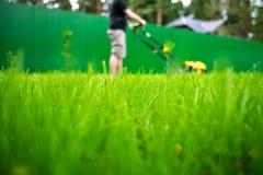 Κοπή ή κοπή της μακριάς χλόης με το θεριστή χορτοταπήτων στο θερινό ήλιο στοκ φωτογραφία με δικαίωμα ελεύθερης χρήσης