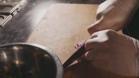 Κοπή αρχιμαγείρων επάνω ένα κρεμμύδι με ένα μαχαίρι φιλμ μικρού μήκους