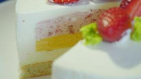 Κοπή ενός γαμήλιου κέικ φραουλών με ένα μαχαίρι Κόψτε το κέικ εξυπηρετούμενο λευκό φραουλών κέικ ανασκόπησης πιάτο φιλμ μικρού μήκους