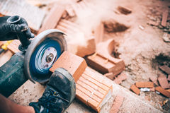 κοπή εργαζομένων μέσω των τούβλων Επαγγελματικό brickmason που χρησιμοποιεί το μύλο στην οικοδόμηση των σπιτιών Στοκ Φωτογραφία
