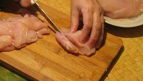 Κοπή κρέατος κοτόπουλου Ο μάγειρας κόβει τη λωρίδα κοτόπουλου στα κομμάτια φιλμ μικρού μήκους