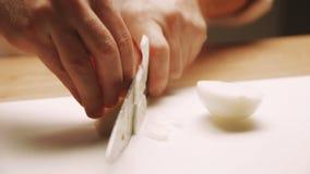 Κοπή μαγείρων επάνω ένα κρεμμύδι με ένα μαχαίρι φιλμ μικρού μήκους