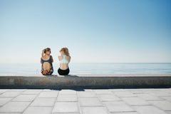 Κορίτσια αθλητικής ικανότητας που χαλαρώνουν μετά από να εκπαιδεύσει υπαίθρια Στοκ Φωτογραφίες