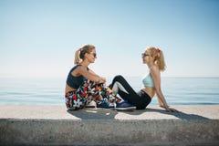 Κορίτσια αθλητικής ικανότητας που χαλαρώνουν μετά από να εκπαιδεύσει υπαίθρια Στοκ Εικόνες