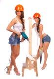 Κορίτσια Διδυμων στα πορτοκαλιά κράνη με ένα πριόνι Στοκ φωτογραφία με δικαίωμα ελεύθερης χρήσης