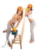 Κορίτσια Διδυμων στα πορτοκαλιά κράνη Στοκ Εικόνες