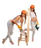 Κορίτσια Διδυμων στα πορτοκαλιά κράνη Στοκ Φωτογραφία