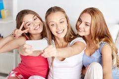 Κορίτσια εφήβων με το smartphone που παίρνουν selfie στο σπίτι στοκ φωτογραφίες