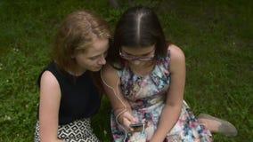 Κορίτσια εφήβων που ακούνε τη μουσική με το κινητό τηλέφωνο φιλμ μικρού μήκους