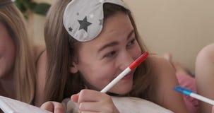 Κορίτσια εφήβων που γράφουν τον κατάλογο αγορών μαζί σχετικά με το σημειωματάριο απόθεμα βίντεο