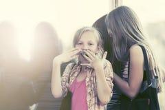 Κορίτσια εφήβων που κοιτάζουν μέσω του παραθύρου λεωφόρων στοκ εικόνα