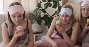 Κορίτσια εφήβων που προσέχουν τον κινηματογράφο και που τρώνε cupcake κατά τη διάρκεια του κόμματος πυτζαμών απόθεμα βίντεο
