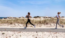 Κορίτσια ικανότητας που τρέχουν στην παραλία Στοκ Εικόνα