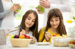Κορίτσια διδύμων που διακοσμούν τα αυγά Πάσχας Στοκ φωτογραφία με δικαίωμα ελεύθερης χρήσης