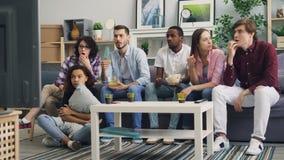 Κορίτσια και τύποι που κουβεντιάζουν στο σπίτι τις ειδήσεις έπειτα προσοχής στη TV που συζητά την τραγωδία απόθεμα βίντεο