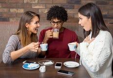 Κορίτσια κουτσομπολιού που μιλούν στον καφέ ενώ το άτομο τρυπιέται Στοκ φωτογραφίες με δικαίωμα ελεύθερης χρήσης