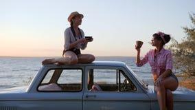 Κορίτσια με τα φλυτζάνια στα χέρια στο όχημα στην προκυμαία στο ηλιοβασίλεμα, κόμμα τσαγιού των φίλων στη μηχανή στη θάλασσα ακτώ απόθεμα βίντεο