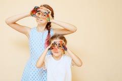 Κορίτσια με τα χρωματισμένα χέρια που κάνουν τη μορφή καρδιών στοκ εικόνες