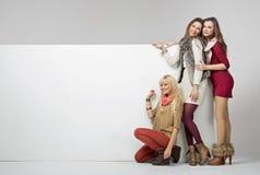 Κορίτσια μόδας με ένα κενό χαρτόνι Στοκ Φωτογραφίες