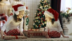 Κορίτσια παιδιών που ανοίγουν τα δώρα Χριστουγέννων φιλμ μικρού μήκους