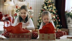 Κορίτσια παιδιών που ανοίγουν τα δώρα Χριστουγέννων απόθεμα βίντεο