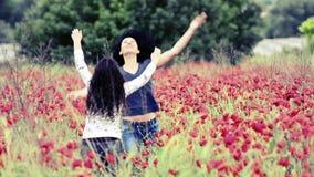 Κορίτσια που έχουν τη διασκέδαση σε έναν τομέα των λουλουδιών φιλμ μικρού μήκους
