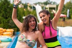 Κορίτσια που έχουν τη διασκέδαση στο πάρκο νερού διασκέδασης, θερινό καυτό ημερησίως στοκ εικόνες