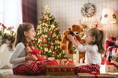 Κορίτσια που ανοίγουν τα δώρα Χριστουγέννων στοκ φωτογραφία