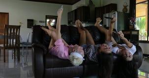 Κορίτσια που βρίσκονται στον καναπέ που παίρνει ανάποδα τη φωτογραφία Selfie στο κύτταρο SmartPphone Laughig εύθυμο στο σύγχρονο  φιλμ μικρού μήκους