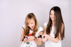 Κορίτσια που γελούν και που κρατούν στη στιλβωτική ουσία καρφιών χεριών Στοκ Εικόνες