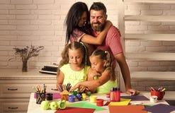 Κορίτσια που επισύρουν την προσοχή με τα ζωηρόχρωμους χρώματα, τους δείκτες και το μολύβι στον πίνακα στοκ εικόνες
