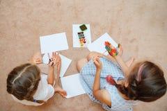Κορίτσια που επισύρουν την προσοχή με τα watercolors σε χαρτί και σε ετοιμότητα στοκ φωτογραφία με δικαίωμα ελεύθερης χρήσης