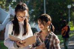 Κορίτσια που διαβάζουν το βιβλίο και το χαμόγελο Στοκ εικόνα με δικαίωμα ελεύθερης χρήσης