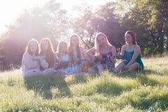 Κορίτσια που κάθονται μαζί στην τραγουδώντας και παίζοντας μουσική χλοωδών τομέων Στοκ φωτογραφία με δικαίωμα ελεύθερης χρήσης