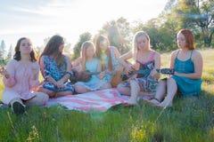 Κορίτσια που κάθονται μαζί στην τραγουδώντας και παίζοντας μουσική χλοωδών τομέων Στοκ Φωτογραφίες