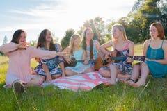 Κορίτσια που κάθονται μαζί στην τραγουδώντας και παίζοντας μουσική χλοωδών τομέων Στοκ εικόνες με δικαίωμα ελεύθερης χρήσης