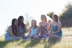 Κορίτσια που κάθονται μαζί στο χλοώδη τομέα με το φως του ήλιου από πάνω Στοκ Εικόνες