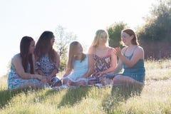 Κορίτσια που κάθονται μαζί στο χλοώδη τομέα με το φως του ήλιου από πάνω Στοκ φωτογραφία με δικαίωμα ελεύθερης χρήσης