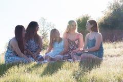 Κορίτσια που κάθονται μαζί στο χλοώδη τομέα με το φως του ήλιου από πάνω Στοκ εικόνα με δικαίωμα ελεύθερης χρήσης